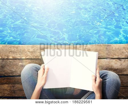 Woman reading book on wooden pier near water