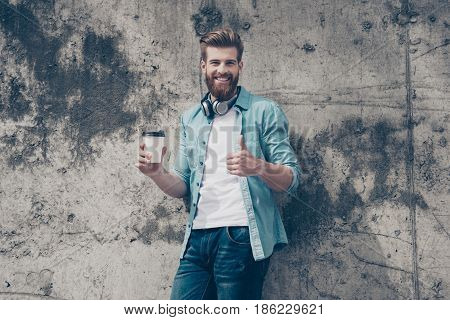 Young Cheerful And Stylish Handsome Red Bearded Man Is Enjoying His Day Off Outside With Coffee And