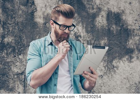 Young Pensive Nerdy Bearded Man In Casual Outfit Is Browsing Info Outdoors. Very Stylish And So Seri