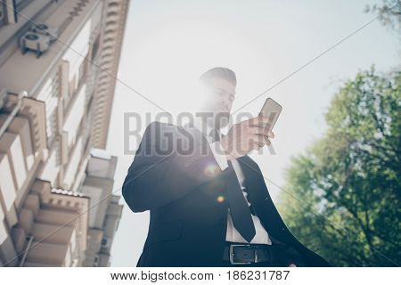 Low Angle View Of A Young Business Man In A Classy Suit Is Checking His Timetable By Pda On The Stre