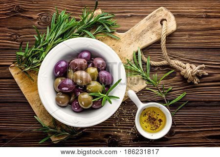 Olives in bowl with olive oil on dark wooden rustic background above view; italian cuisine