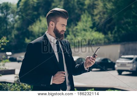 Young Stylish Bearded Business Man In A Classy Suit Is Browsing His Pda On The Street At The Sunny D