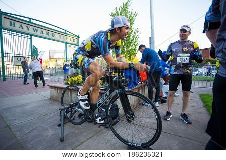 EUGENE, OR - MAY 7, 2017: Triathlete rides his bike on a stationary trainer to stay warm before the start of the 2017 Eugene Marathon race held on the University of Oregon campus.