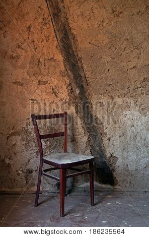 Old wooden chair against a background of shabby walls. Sepia color dominates.