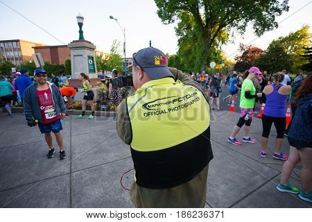 EUGENE, OR - MAY 7, 2017: Sports photographer with a yellow vest captures an image of a runner prior to the start of the 2017 Eugene Marathon race held on the University of Oregon campus.