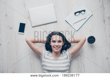 Top View Of Girl Resting On The Floor After Working Hard. She Is Happy, Her Hands Are Behind The Hea