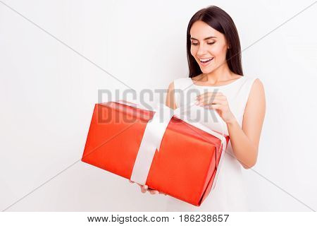 Happy Amazed Gorgeous Brunette Is Holding Big Red Present Box On White Background. She Is Smiling, D
