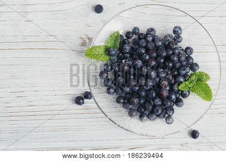 Fresh bilberry on glass plate. Healthy breakfast.