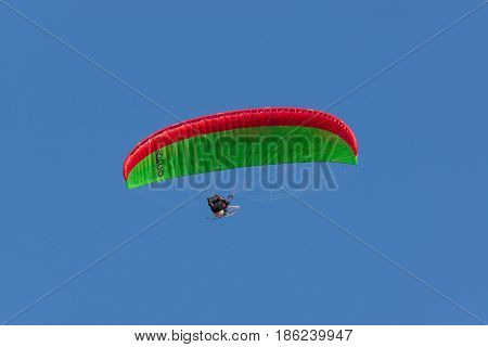 Wales UK - May 10 2017: APCO paramotor wing and pilot a powered paraglider with a two stroke engine and propeller in a frame attached to the pilot.