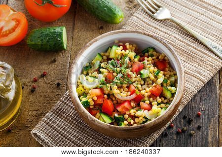 Healthy salad for breakfast made of couscous tomatoes cucumber and onion on a table. Traditional Israeli Ptitim meal. Moroccan cuisine food. Top view.