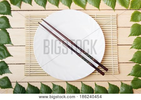 Empty plate on a bamboo mat with chopsticks top view on a wooden background framed with leaves of a tree