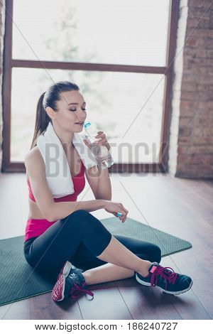 Exhausted Cute Sportwoman Finished Her Work Out And Now Drinking Water. She Is Sitting On The Mat Wi