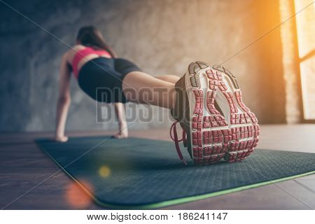 Close Up Of Sneakers Of Sportswoman. She Is Training In Sunny Room On The Green Mat, Wearing Modern