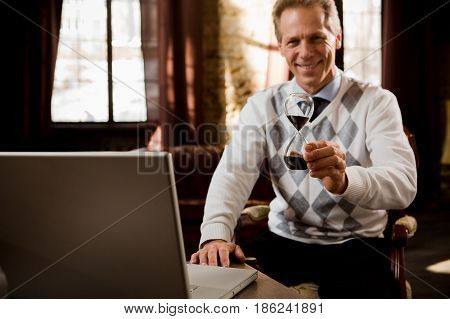 Psychology concept. Psychiatrist man staying in his office and waiting for patients. Psychiatrist man holding hourglass in hand.