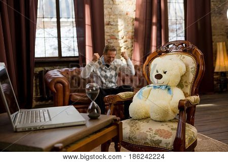 Psychology concept. Handsome man sitting on sofa and expressing his emotions both positive and negative while teddy bear psychiatry listening to him.