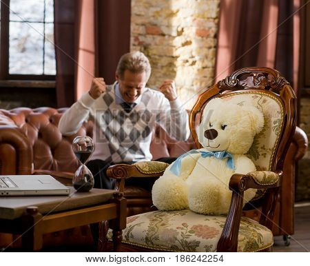 Handsome man sitting on sofa and expressing his emotions both positive and negative. Man telling about his family or work problems while teddy bear psychiatry listening to him. Psychology concept.