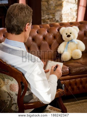 Consultation at psychological office. Psychiatrist man listening to his patient teddy bear and writing his psychological disease.