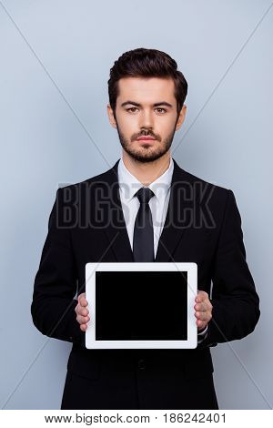 Vertical Portrait Of Serious Confident Businessman In Formalwear Showing Black Touchscreen Of His Di