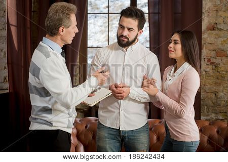 Couple man and woman communicating with psychologist at psychologist's office. Happy man and woman telling about their family problems after marriage.