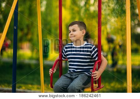 A little boy in a striped T-shirt is playing on the playground, Swing on a swing.Spring, sunny weather.