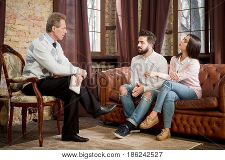 Couple man and woman communicating with psychologist at psychologist's office. Psychiatrist man listening to problems of man and woman. Young people sharing their problems.
