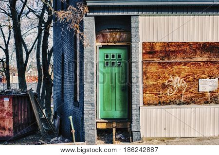 A broken green door in the ghettos.