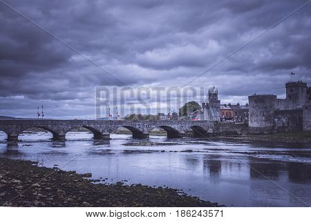King Johns Castle and an old bridge over river Shannon at night, Limerick, Ireland