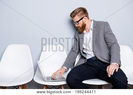 Serious Confident Bearded Business Man Banker In Formal Wear Typing On His Laptop While Waiting In T