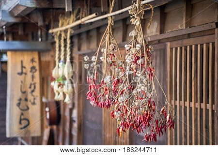 Traditional Japanese red chillies hanging from thatched roof