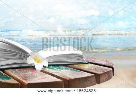 Reading during summer vacation. Book and flower on landscape background