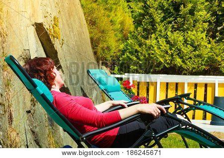Adult Woman Relaxing On Sunbed In Garden