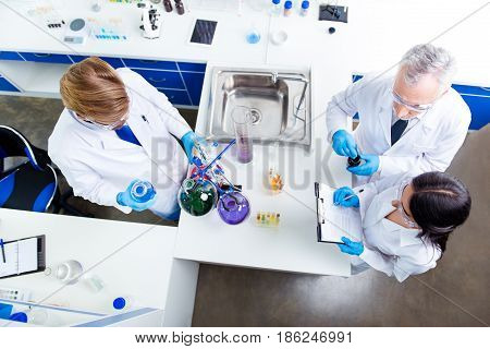 Top View Of Team Work Of Three Scientists, Making Tests With Chemicals In Flasks, Making Notes, All