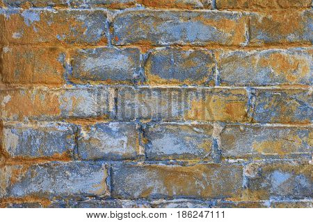 Fragment of old brickwork: bricks blue tint with rusty rust color texture of ancient stone faded wall.