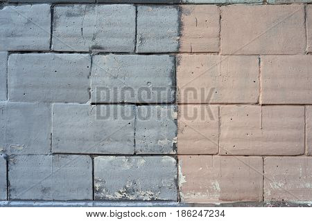 The brick wall painted in two colors: left gray color on the right a faint pink color textures large brickwork.