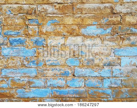 The old brickwork blurred by the weather the blue and yellow colored wall.