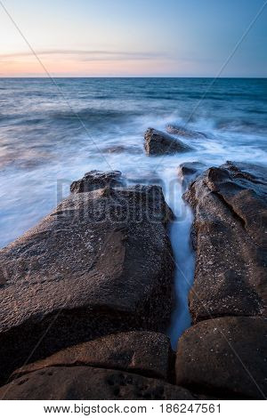 Waves and rocks shore long exposure photo