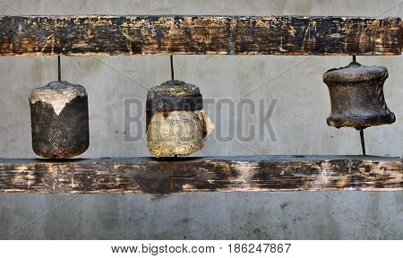 Ancient Buddhist Tibetan prayer drums: three old cylinders covered with leather torn in pieces and fragments of antique paper with prayer texts Tibet.