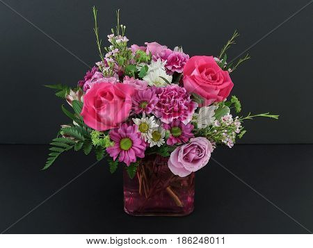 A bouquet of cut flowers is displayed in a clear glass vase through which the stems may be seen in water tinted red.