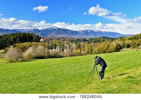 Spring forest and meadows landscape in Slovakia with photographer foreground. Blooming cherry trees. Sunlit country.