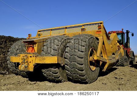 The huge tires and wheels of an earth moving scraper