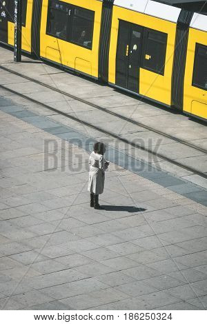 Woman standing alone on the street in front of tramway / tram train