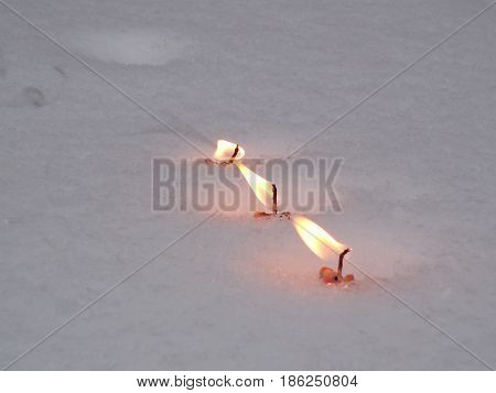 Flames of the candles on the snow background