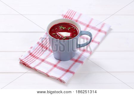 cup of beetroot cream soup on on checkered dishtowel