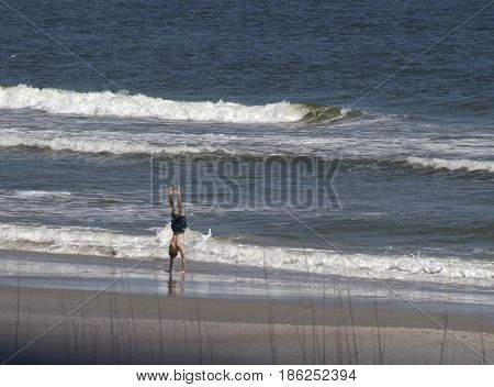 Carolina Beach, North Carolina, USA - April 11, 2017: A young man does an athletic handstand in the water of an incoming ocean tide on a sunny beach