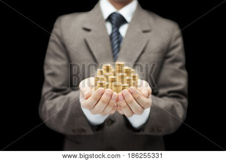 Man holding golden coins in hands on black background