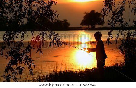 Little boy fishing at dusk.