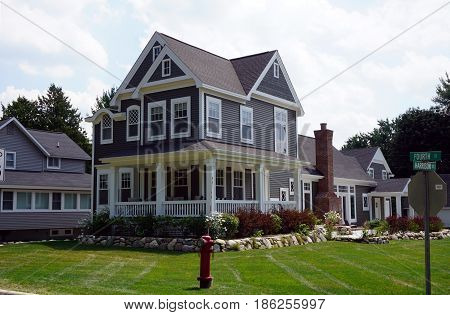 HARBOR SPRINGS, MICHIGAN / UNITED STATES - AUGUST 4, 2016: A large, elegant home, with a wraparound porch, at the corner of Fourth and Harrison Streets in Harbor Springs.