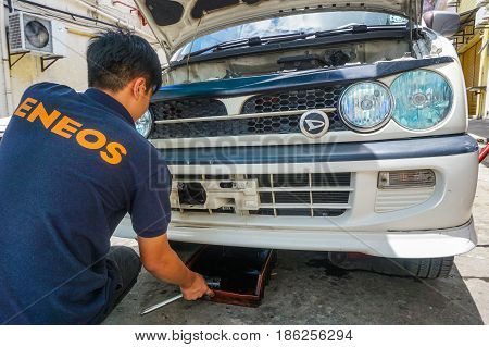Labuan,Malaysia-May 9,2017:Car mechanic changing dirty motor oil & service in automobile engine at service station in Labuan,Malaysia.