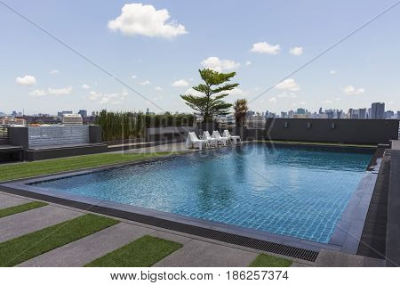 swiming pool on a top of a hotel with white coud and bluy sky background