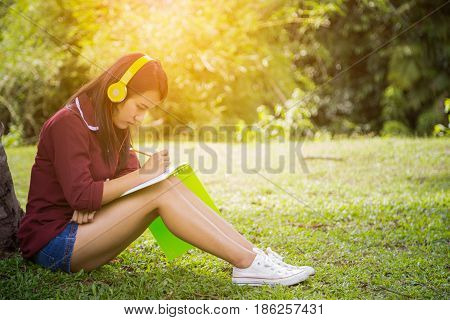 Asian woman listening to music and writing on notebook under the tree